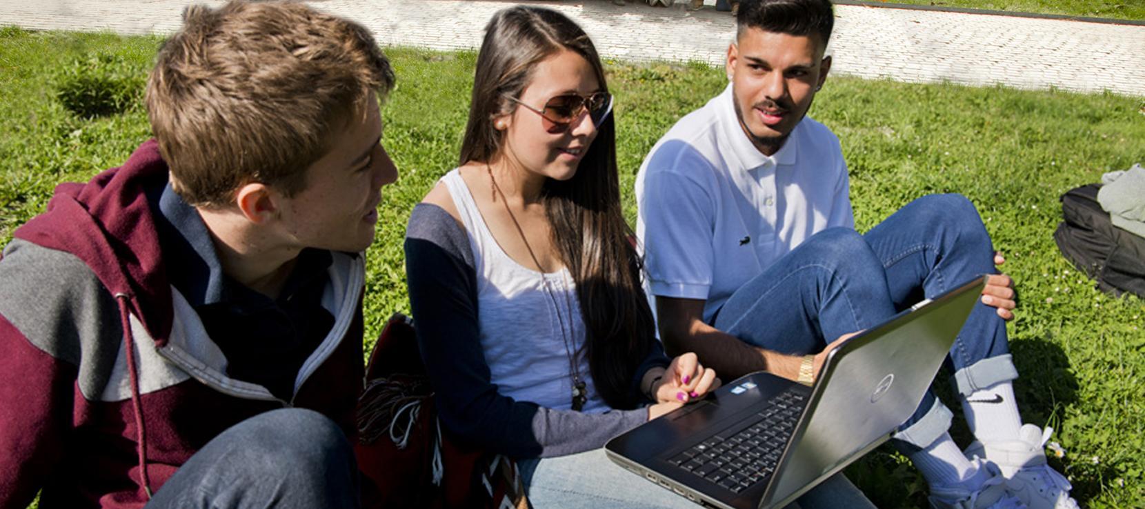 Groupe d'étudiants sur l'esplanade avec ordinateur